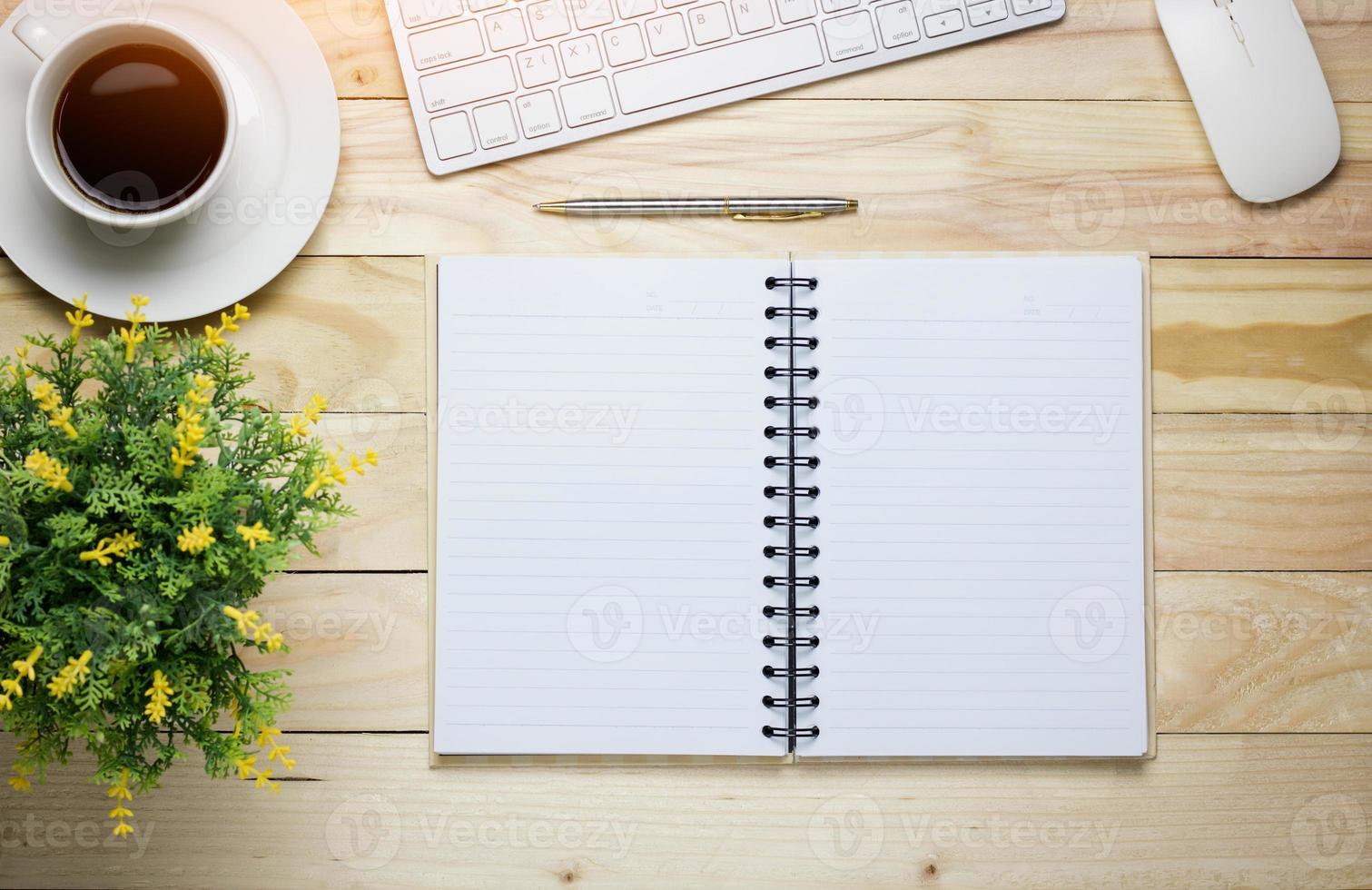 ovanifrån av skrivbordet med anteckningsboken och kaffe foto