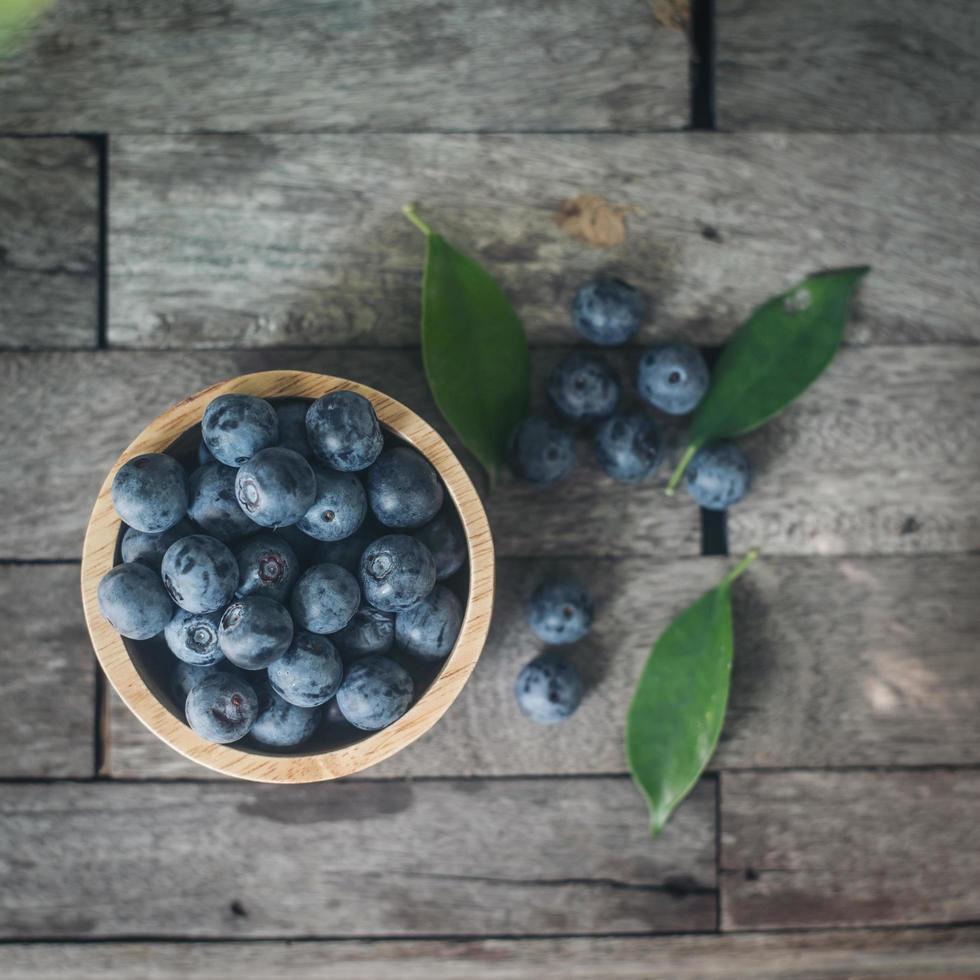 färska plommon i en träskål på gammal träbakgrund foto