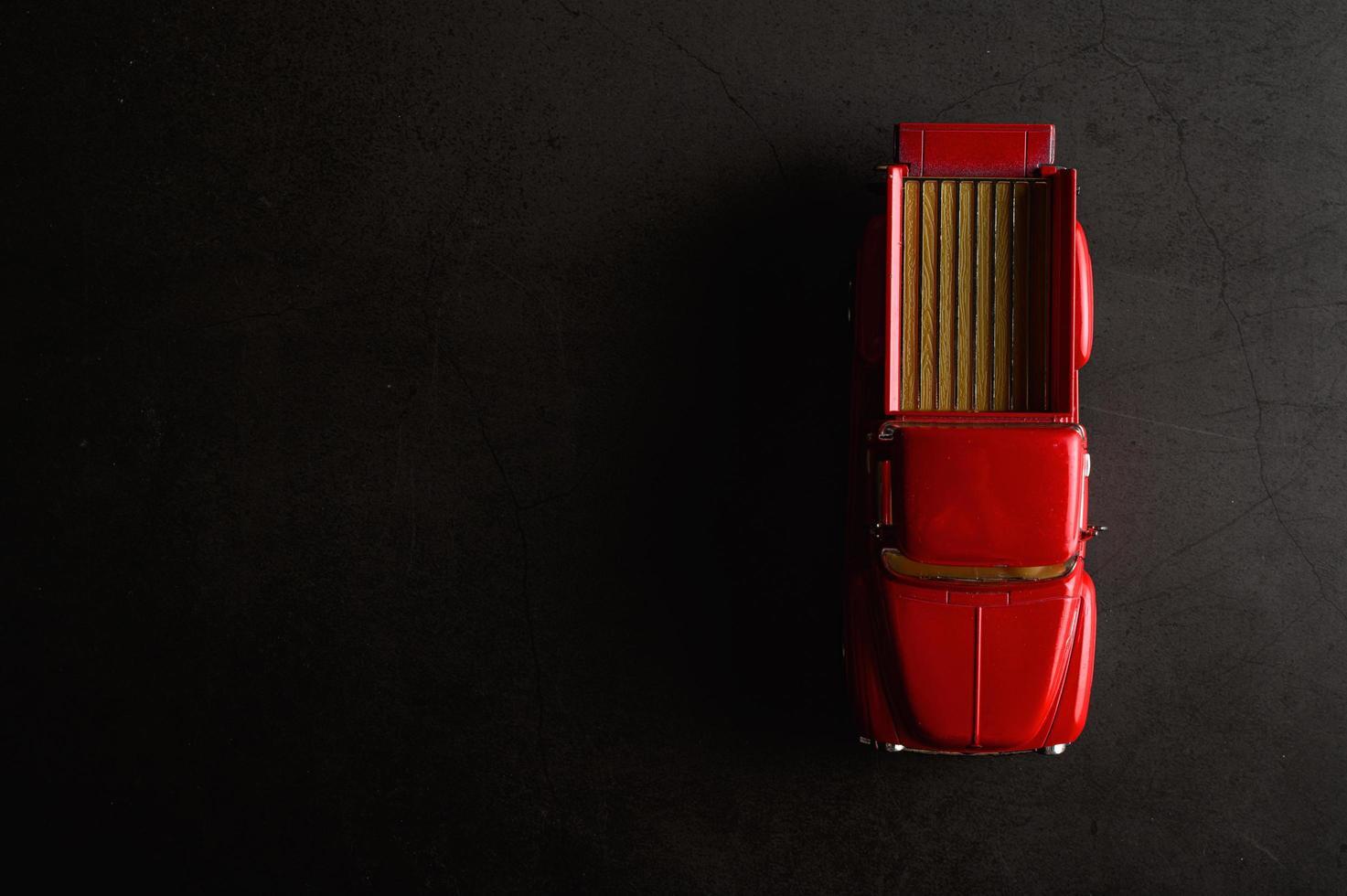 röd pickup modell lastbil på ett svart golv foto
