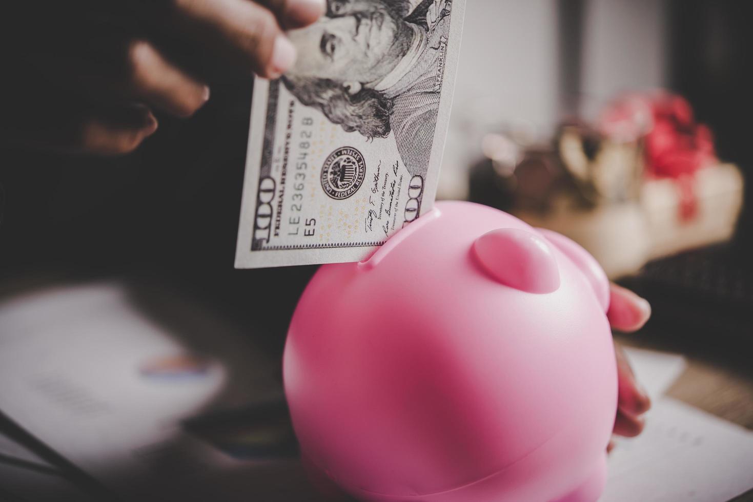 kvinna som sätter eurosedlar i en spargris foto