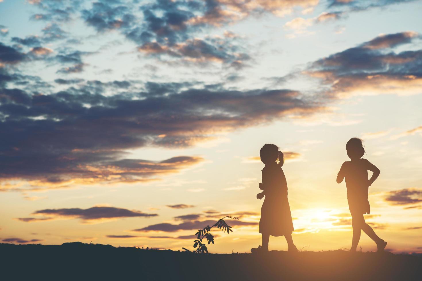 solnedgång silhuett av barn som leker foto