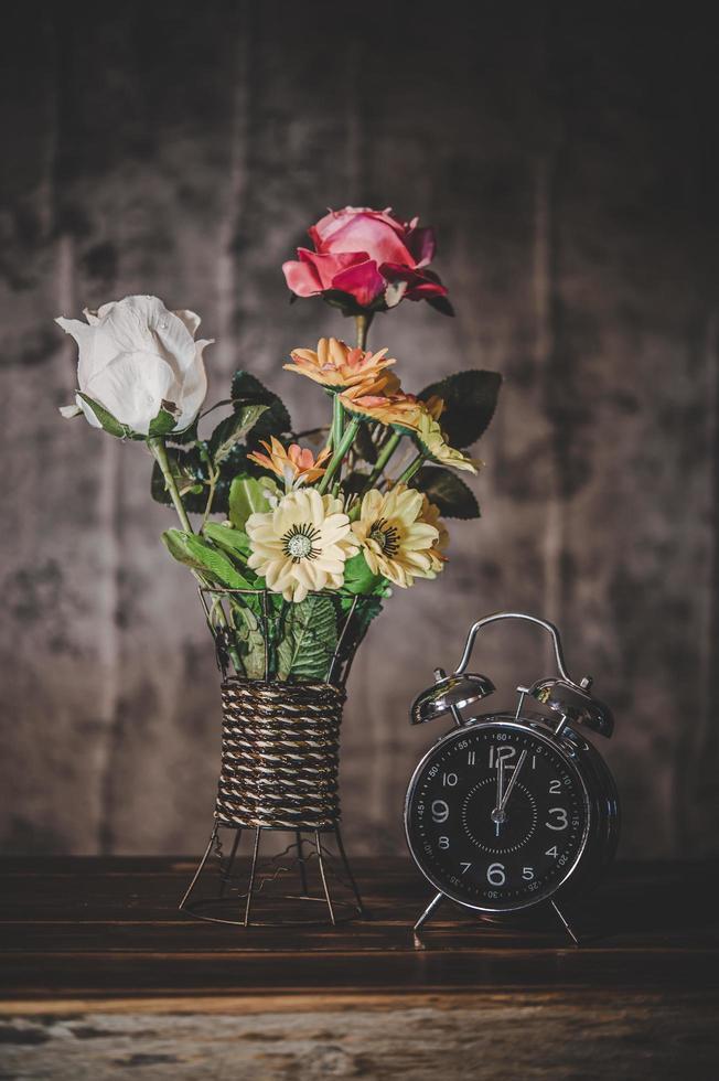 stilleben med blommor och en klocka foto