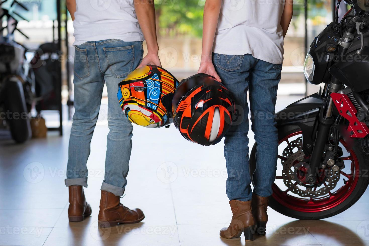 par som håller motorcykelhjälmar foto