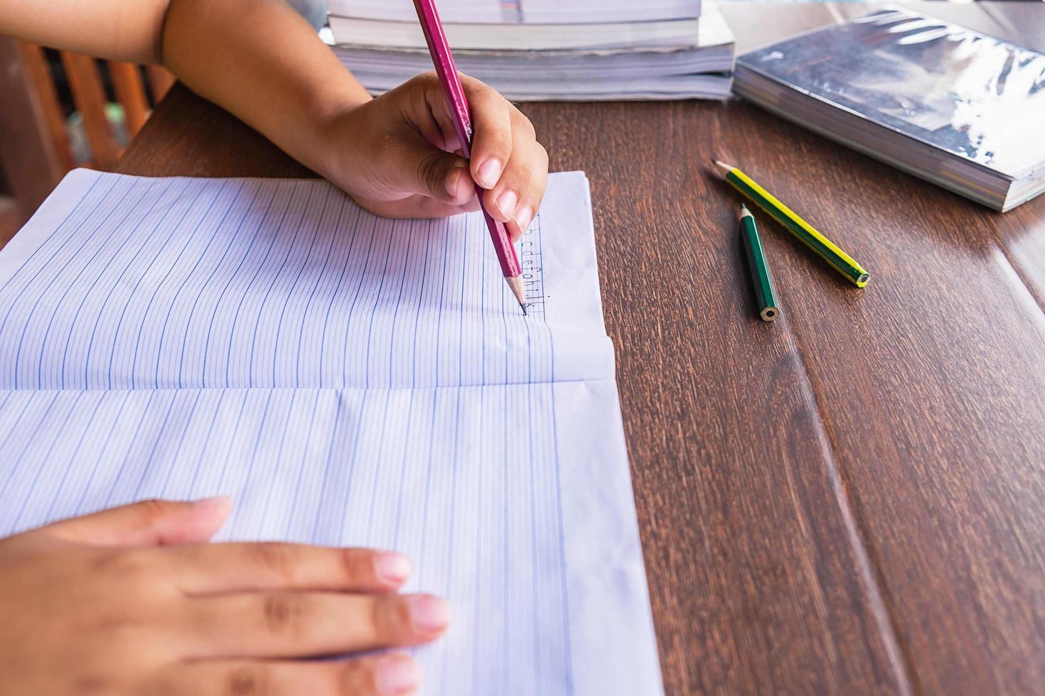 student skriver i en anteckningsbok foto