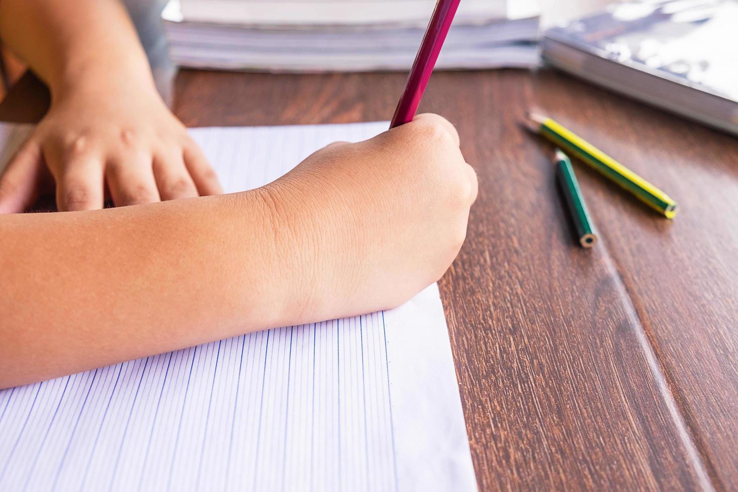 ungen skriver i en anteckningsbok foto