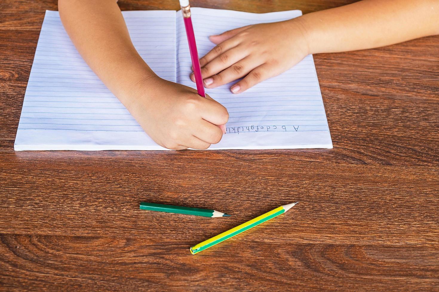 barn som skriver i en anteckningsbok foto