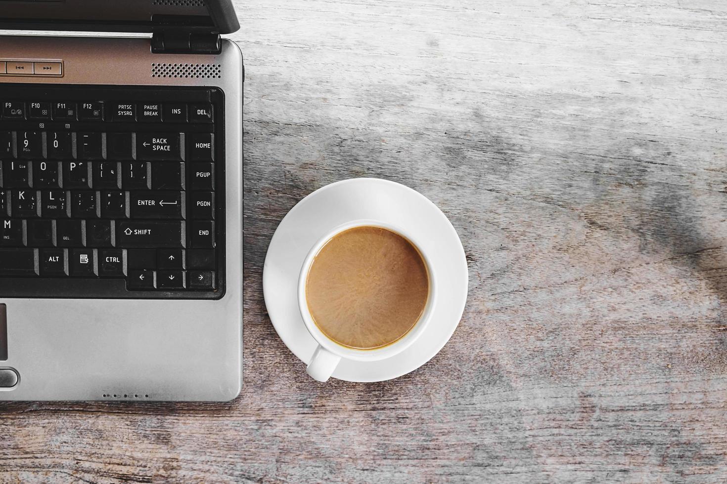 kaffekopp och bärbar dator på ett skrivbord foto