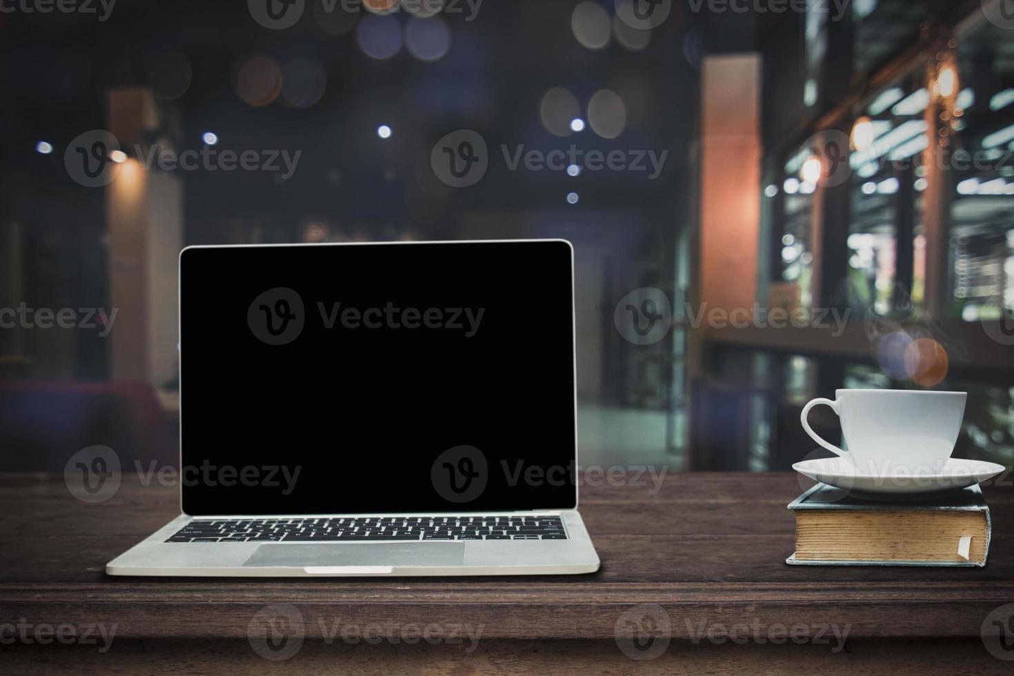 bärbar dator och kaffe med café bakgrund foto