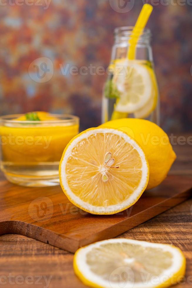 skivade citroner med saft i bakgrunden foto