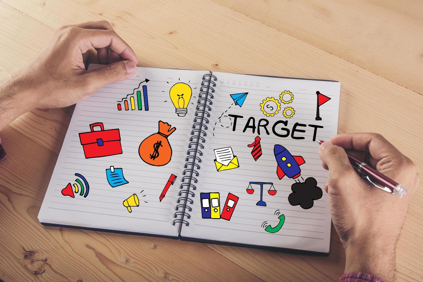 närbild av händer som skriver på papper med färgglada doodle-ikonen för företag foto