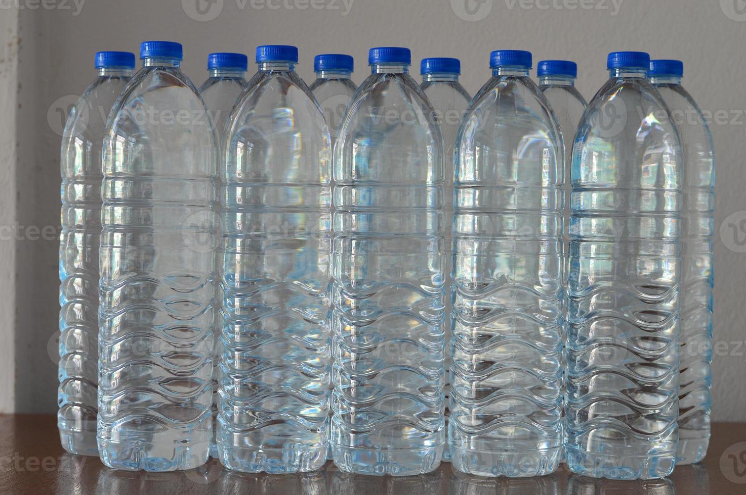 rader av vattenflaskor av plast på bordet foto