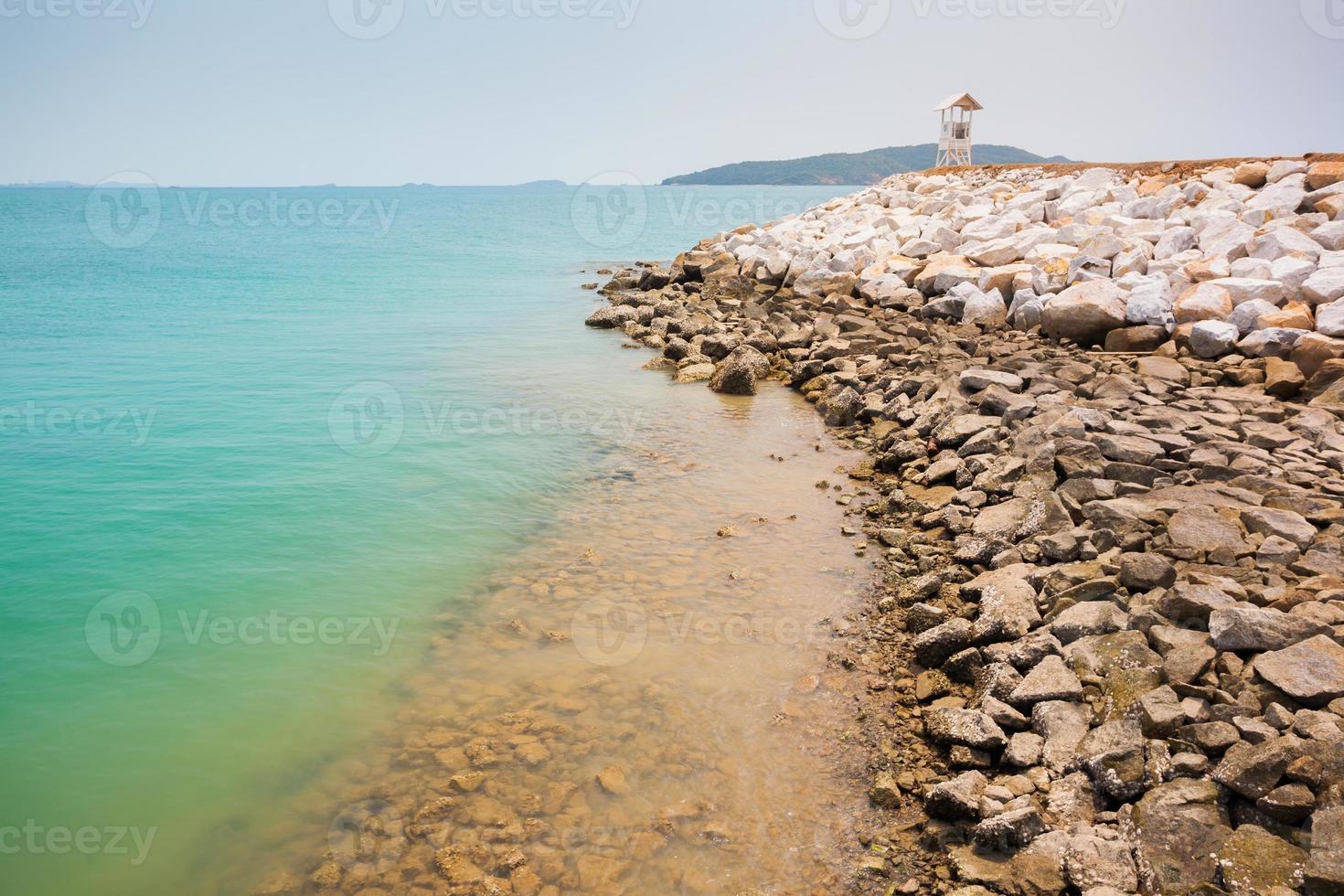 ljusblått hav med en stenig strand foto