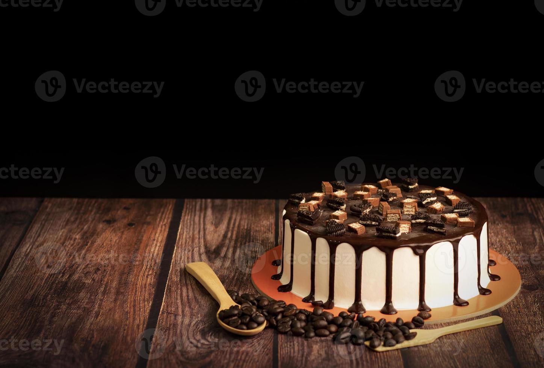 chokladkaka med kaffebönor på träbord foto