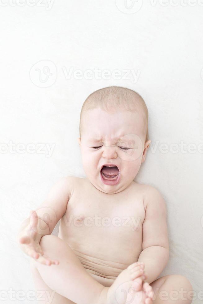 söt flicka som gråter på sängen foto