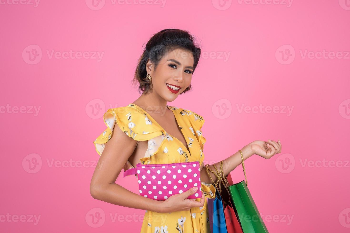 ung moderiktig kvinna som håller en plånbok med kontanter och påsar foto