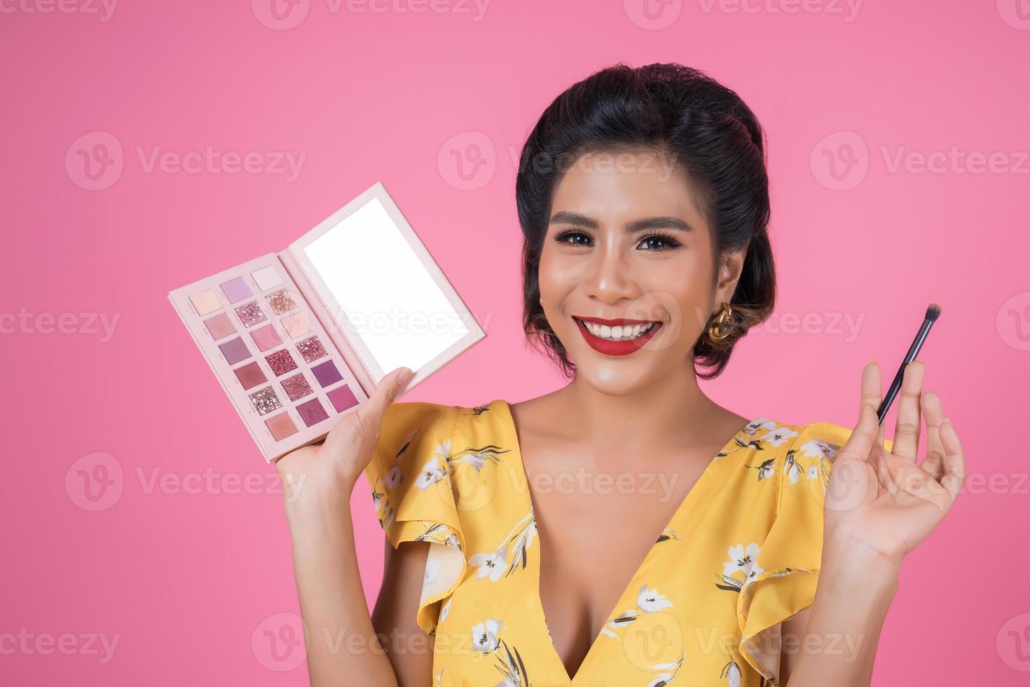 porträtt av kvinna med sminkborste och kosmetika foto
