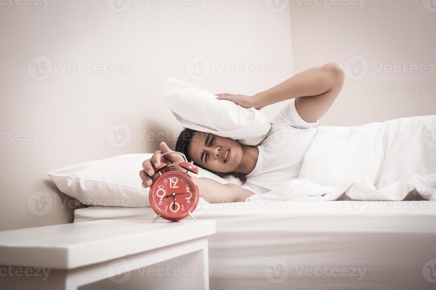 mannen stänger av väckarklockan på morgonen foto