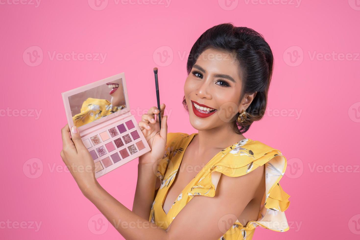 porträtt av en kvinna med smink och kosmetisk borste foto