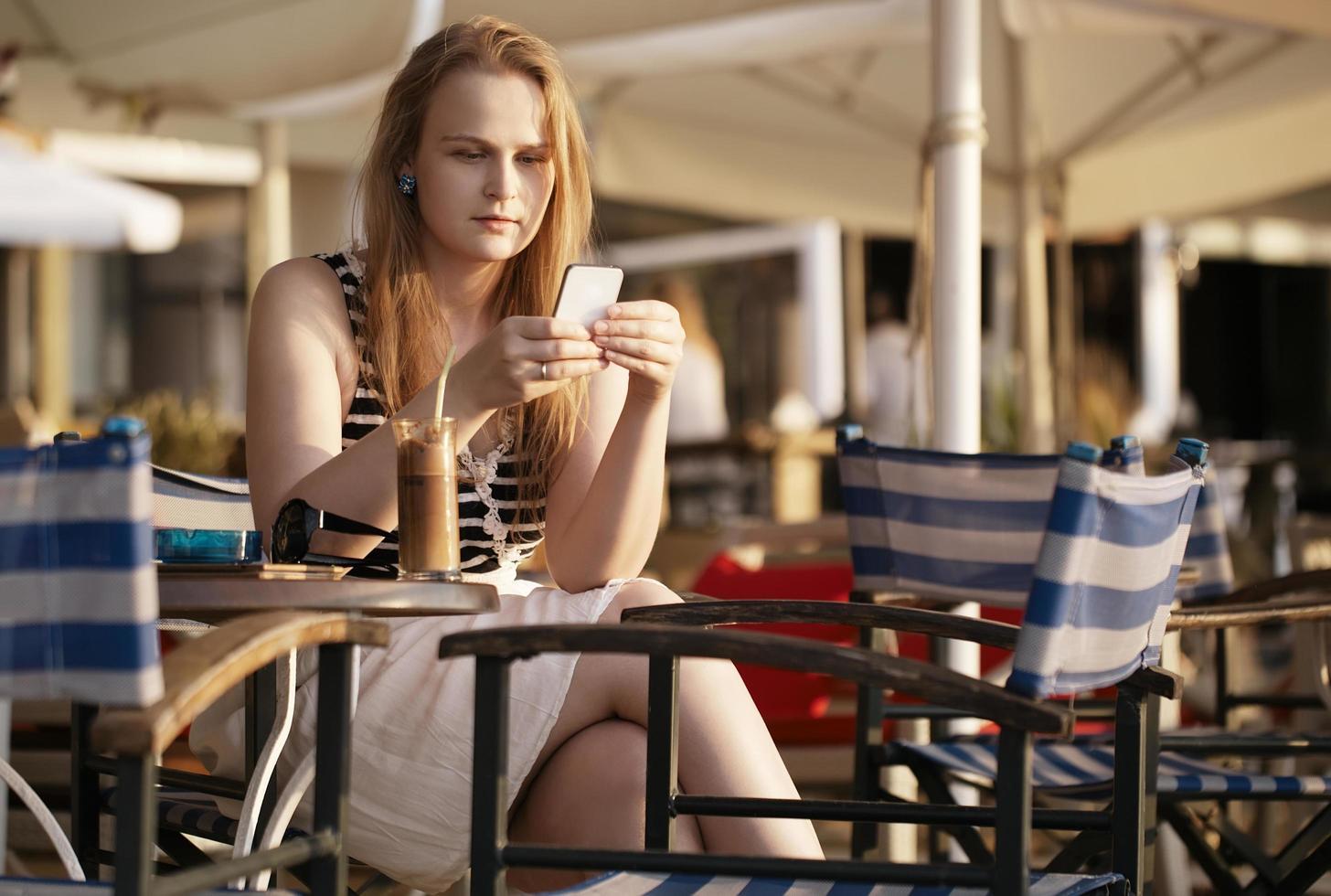 kvinna smsar på sin telefon medan du sitter på ett utomhuscafé foto