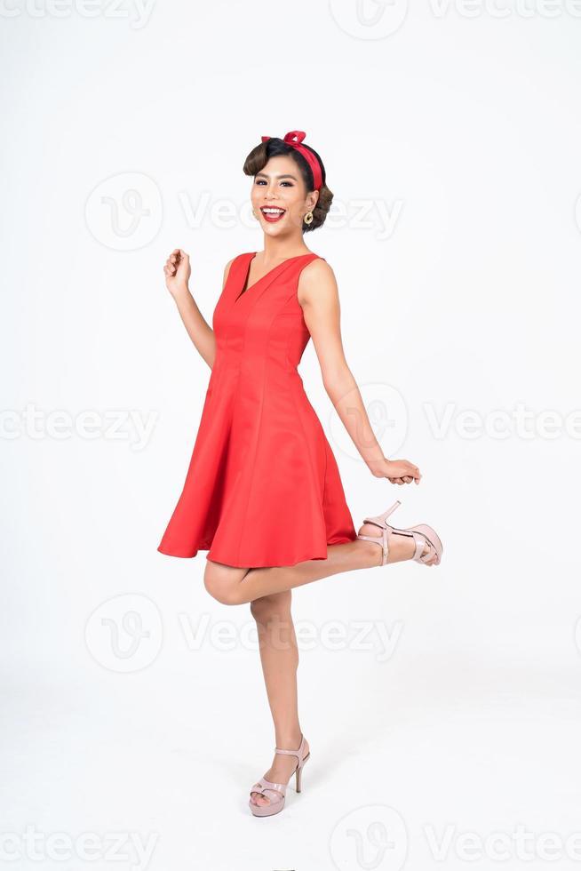 vacker kvinna som bär en röd klänning i studio foto