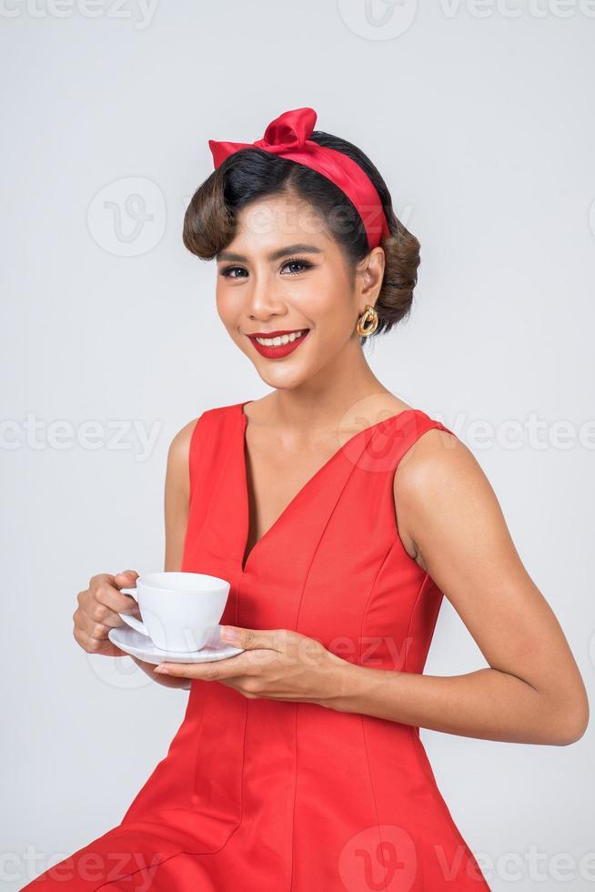 glad moderiktig kvinna som håller en kaffekopp foto