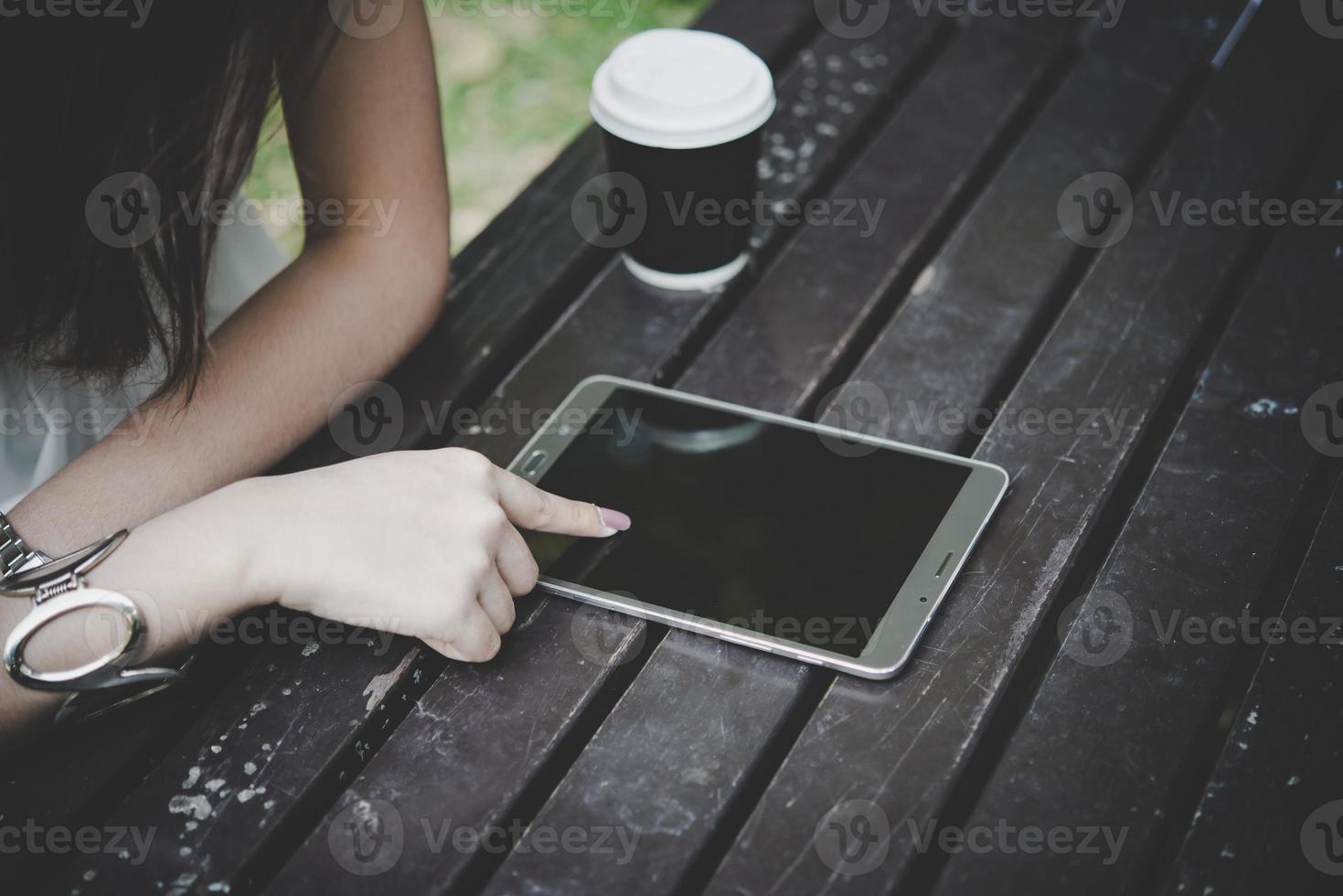 närbild av kvinna med tablettdator på träbord med kopp kaffe foto