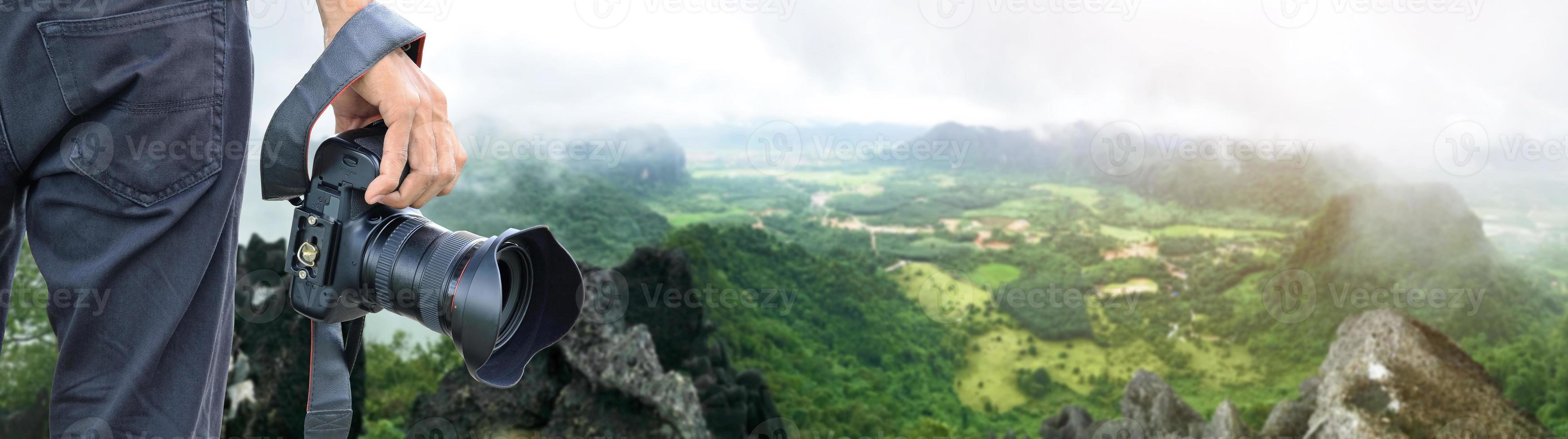 hand som håller digital kamera med utsikt över flygpanorama av grönt landskap foto