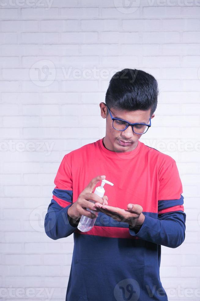 ung asiatisk man som använder desinfektionsvätska för att förhindra koronavirus foto