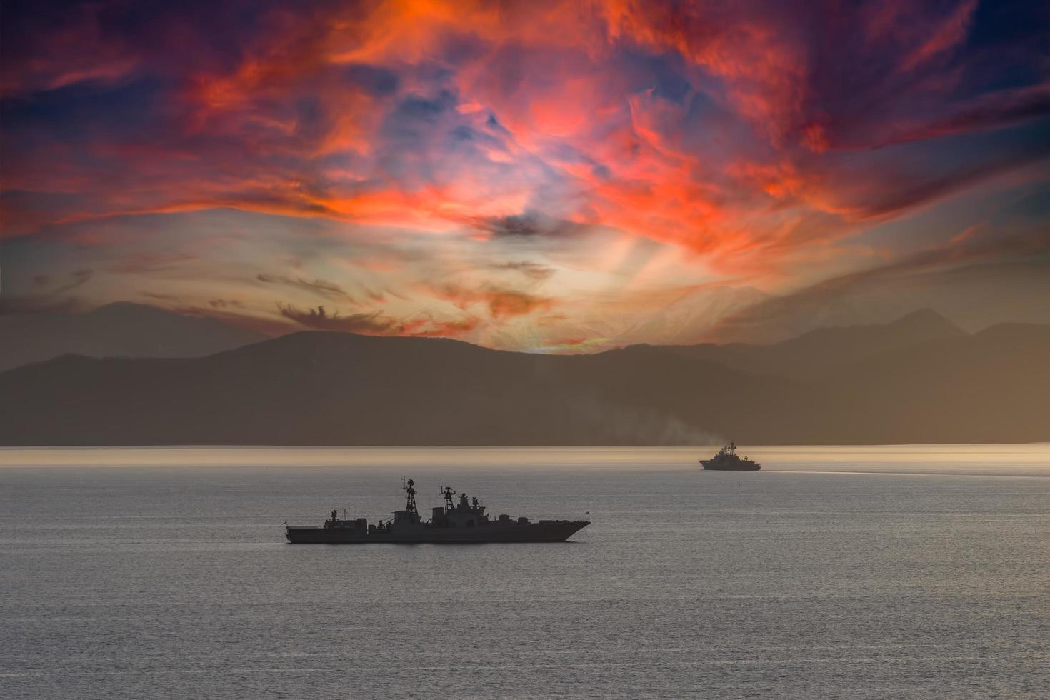 marinmålning med silhuett krigsfartyg i vatten bredvid berg vid solnedgången foto