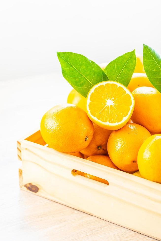 färska apelsiner på ett träbord foto