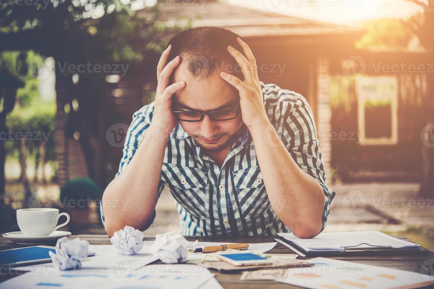stressad affärsman med papper och diagram som sitter vid bordet hemma foto