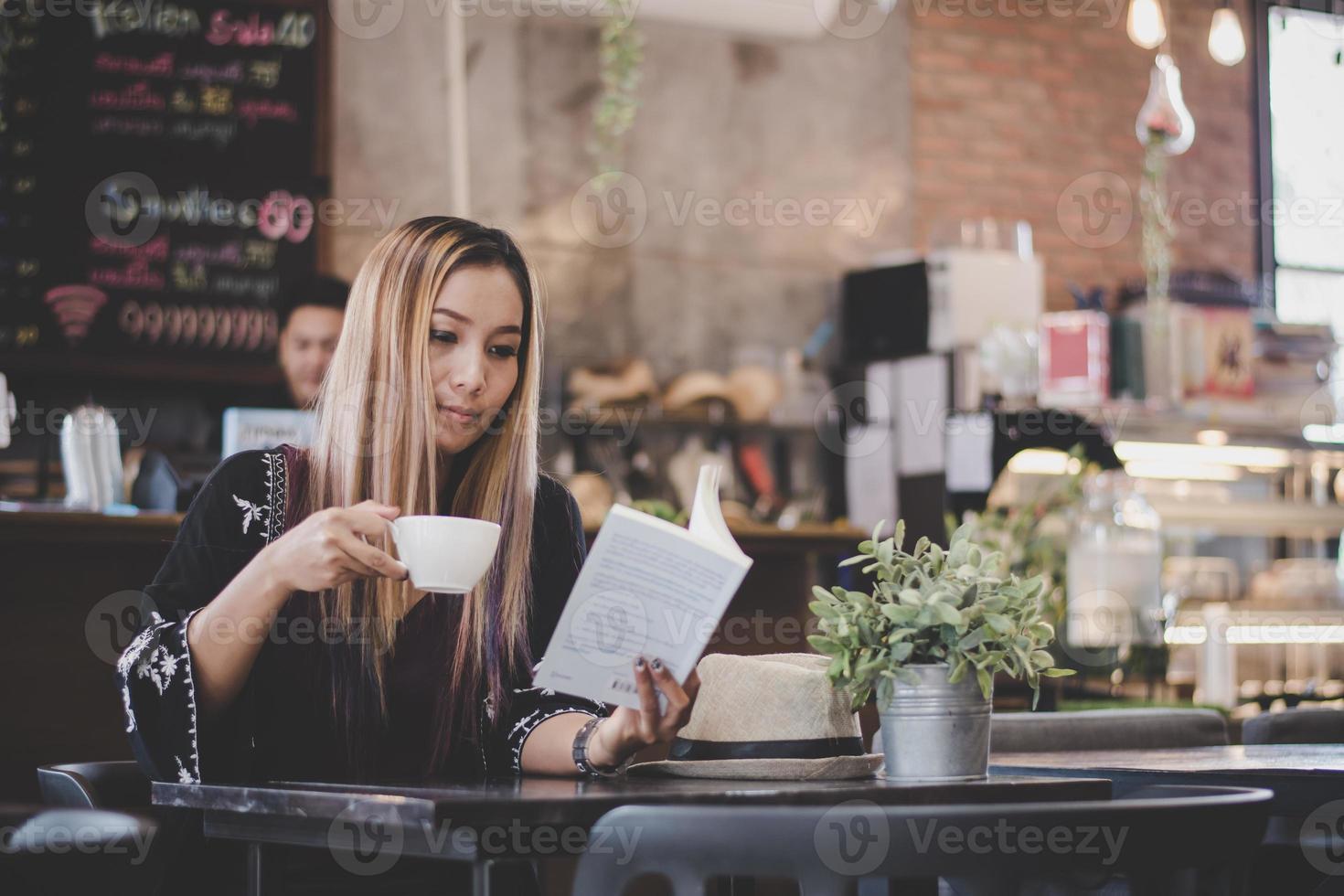 glad affärskvinna som läser en bok medan du kopplar av på caféet foto