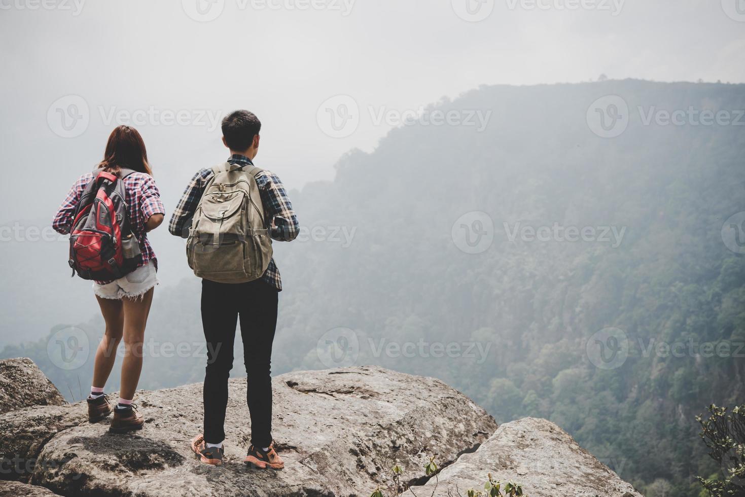 vandrare par med ryggsäckar som står på toppen av ett berg och njuter av naturen foto