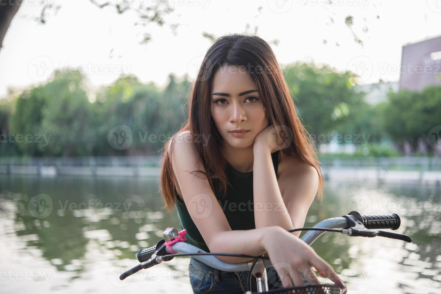 vacker ung kvinna som cyklar i grön park foto