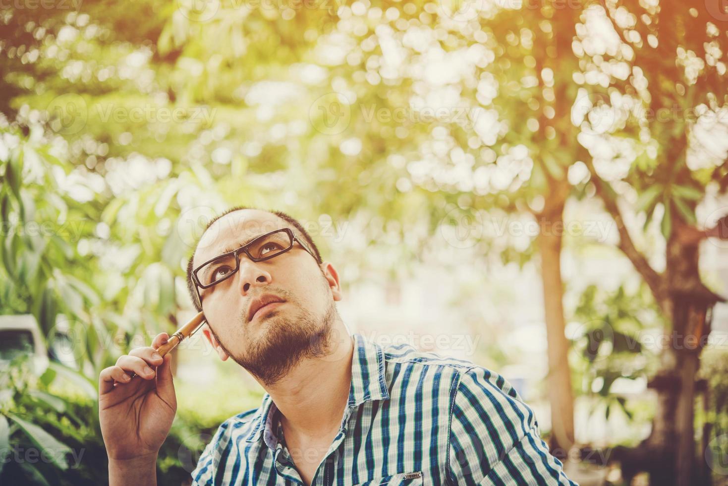 affärsman funderar på något med penna på huvudet medan han arbetar hemma foto