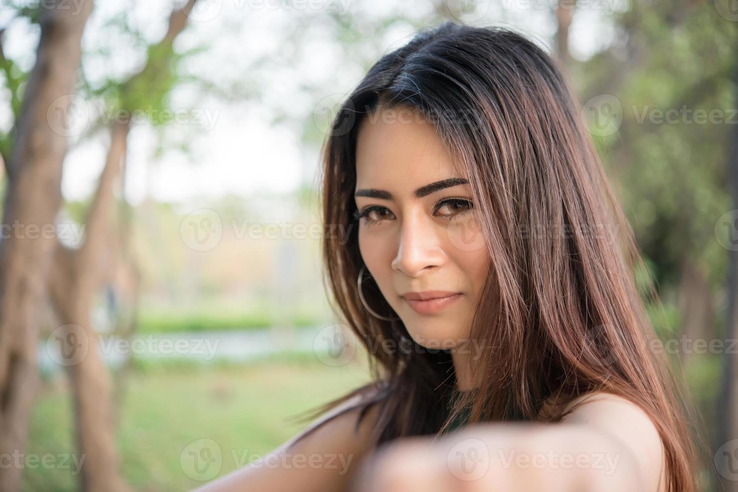 porträtt av en leende flicka som kopplar av i naturen parkerar utomhus foto