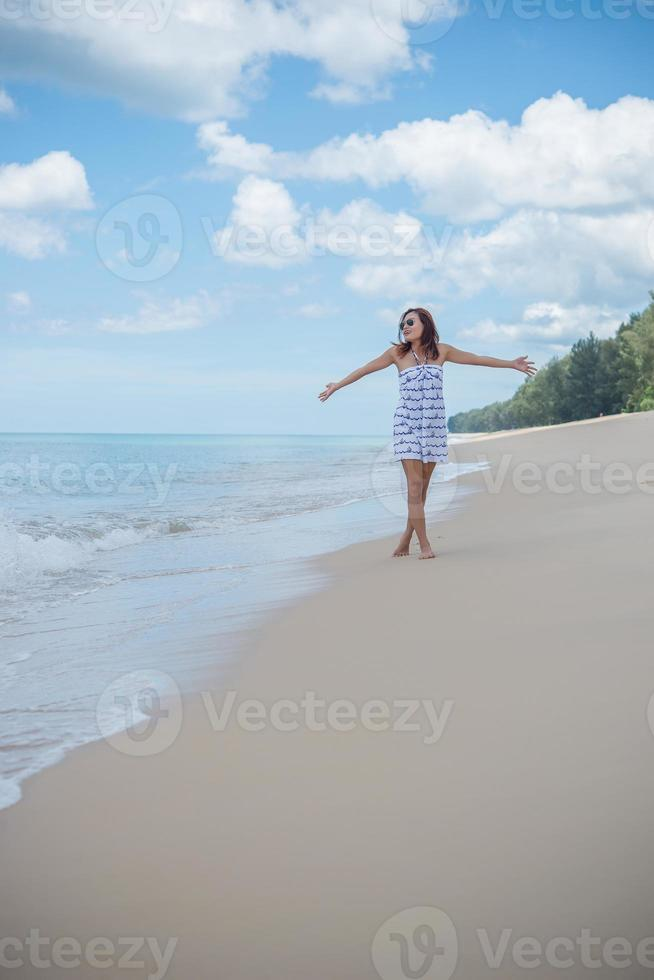 ung vacker glad kvinna njuter av stranden foto