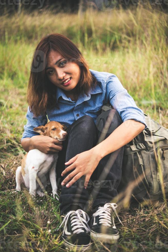 ung kvinna som sitter i gräset med sin lilla hund under solnedgången foto
