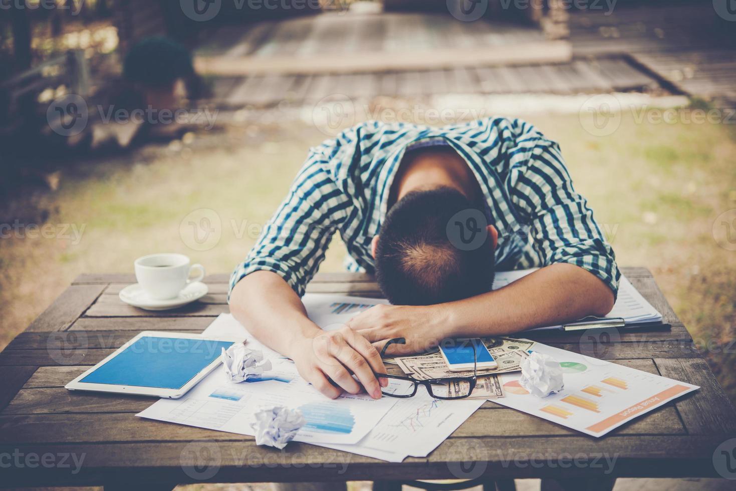 trött arbetande man som sover på arbetsplatsen full av arbete foto