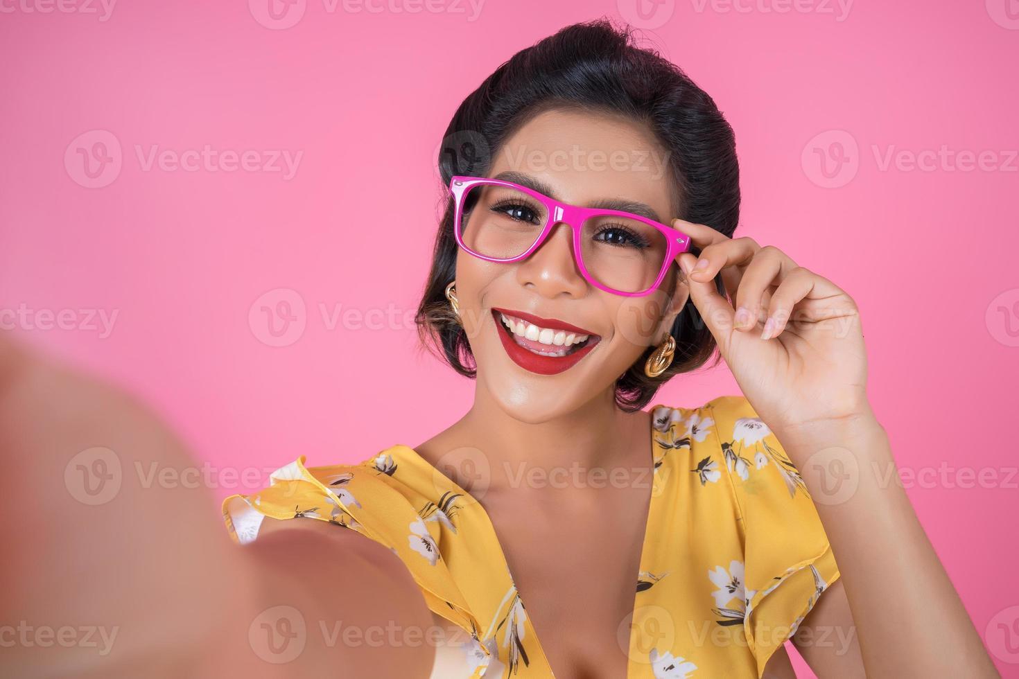 vacker fashionabla kvinna tar en selfie med sin telefon foto