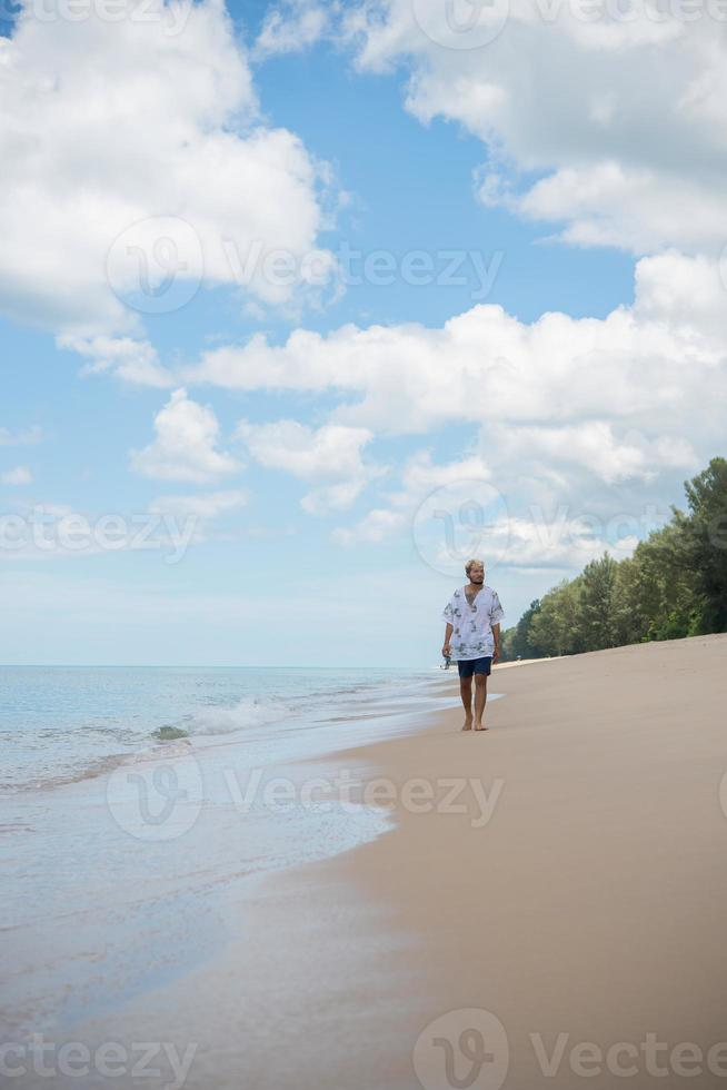 hipster man går på bakgrunden av vackra stranden med vita moln och fin himmel foto