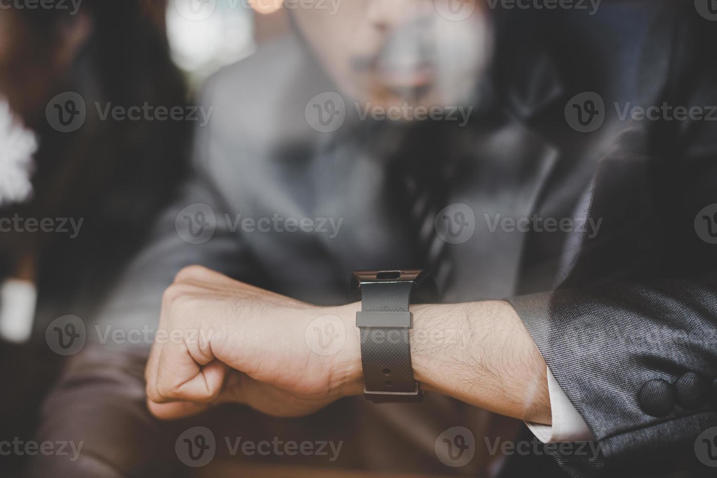 ung affärsman som sitter på cafébaren och tittar på klockan foto