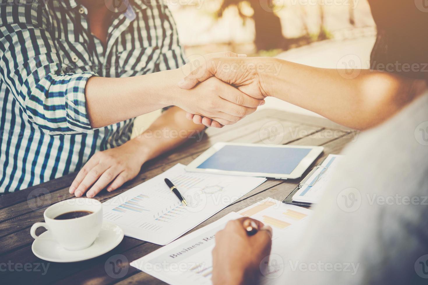 närbild av två affärsmän som skakar hand medan du sitter på arbetsplatsen foto