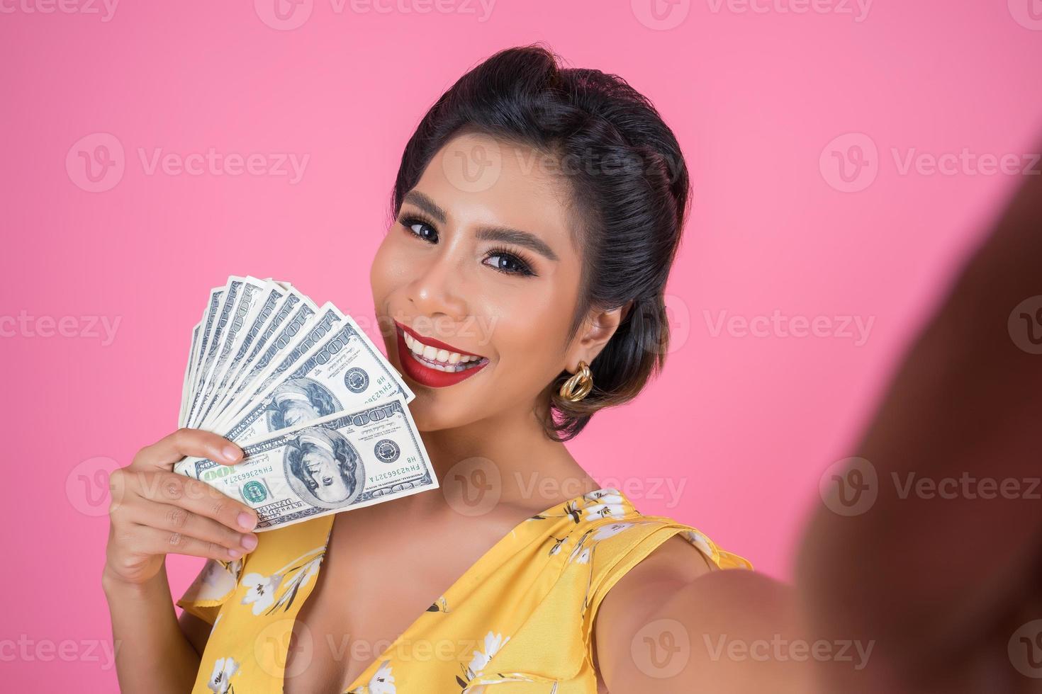glad moderiktig kvinna som håller pengar foto
