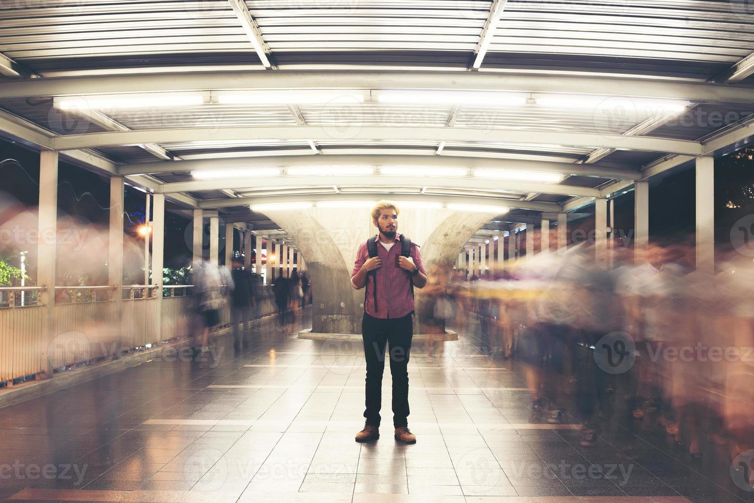 stilig skäggig man med ryggsäck som står på gatan som reser på natten foto