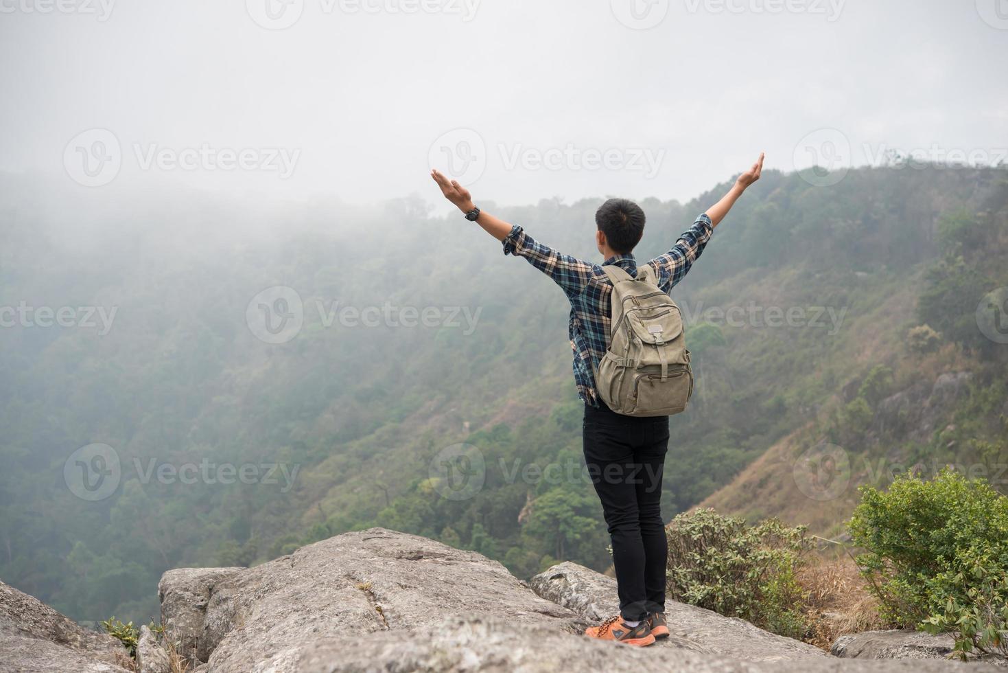 vandrare med ryggsäck som står på toppen av ett berg med upphöjda händer foto