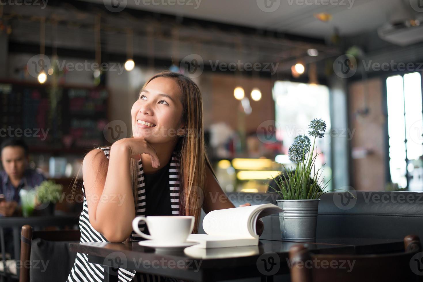asiatisk kvinna som kopplar av och läser en bok på kaféet foto