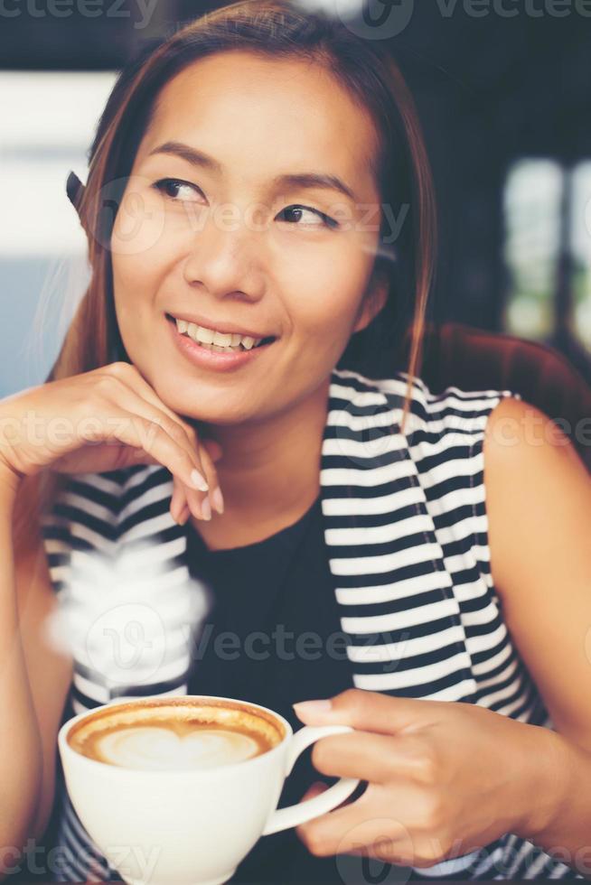 asiatisk kvinna som kopplar av med kaffe på kaféet foto