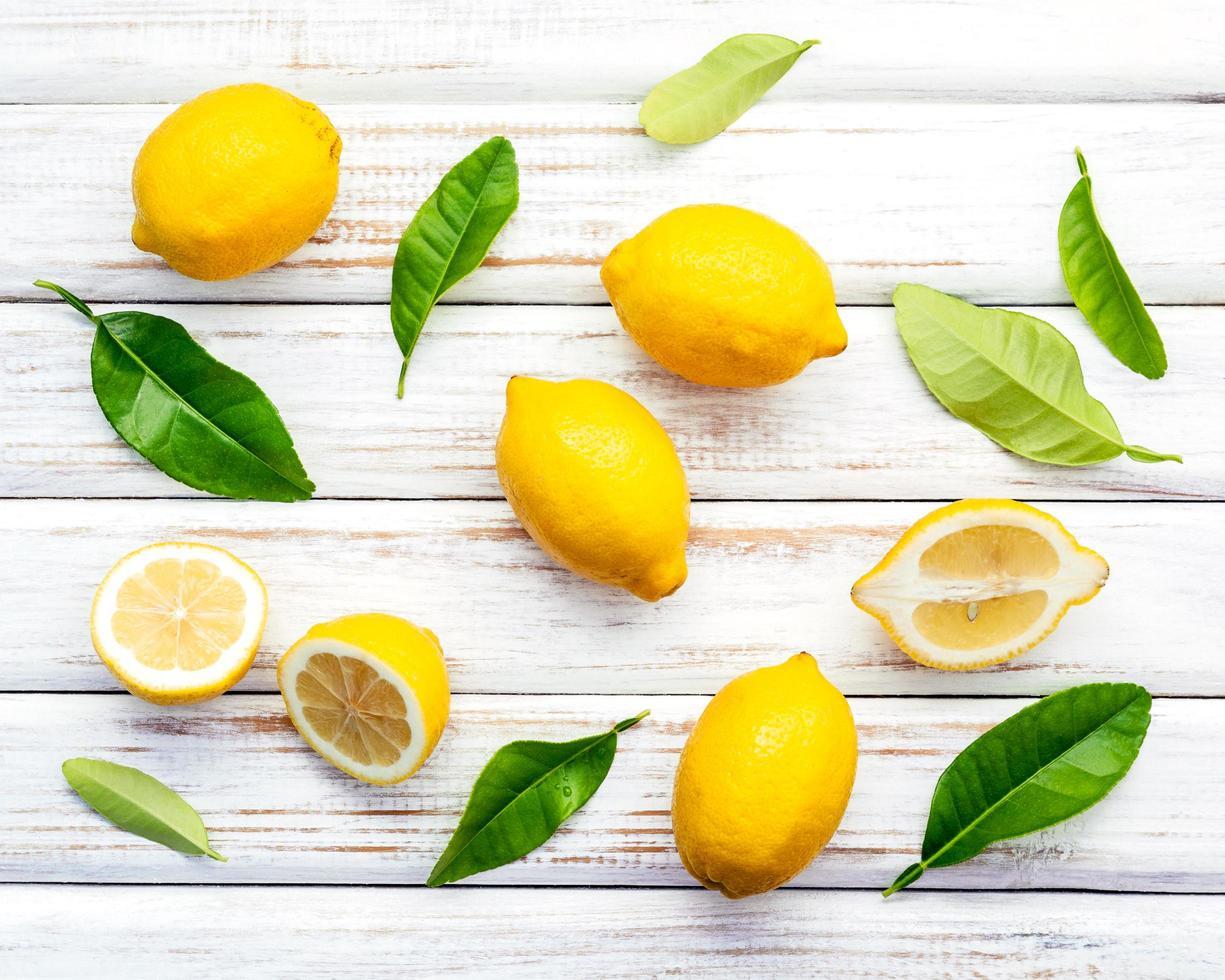 färska citroner och blad på en rustik vit träbakgrund foto
