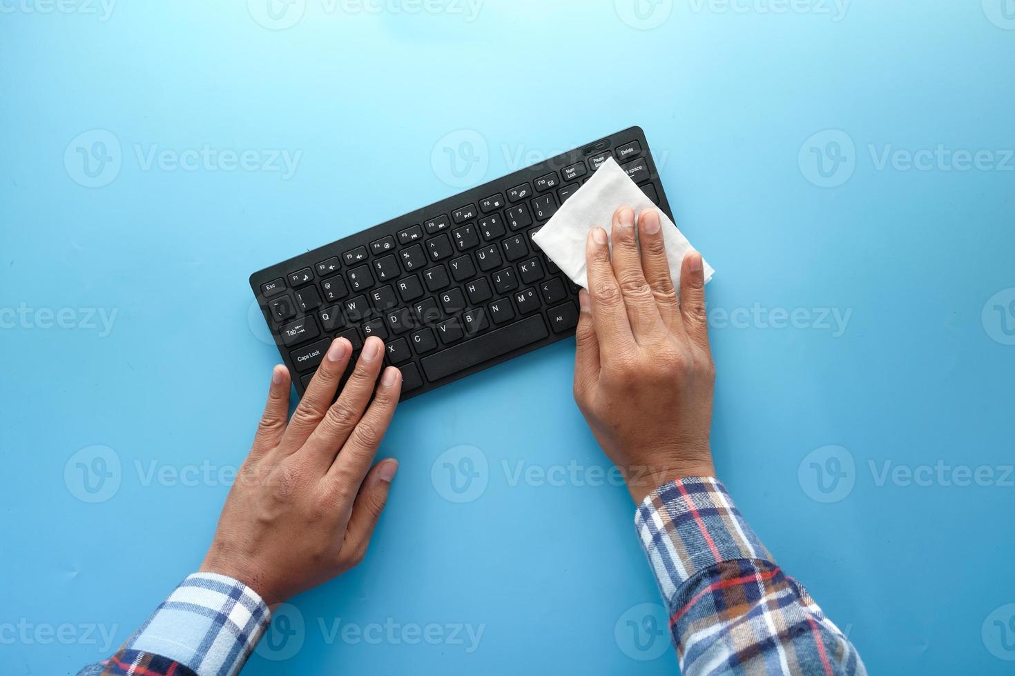 händer som rengör ett tangentbord foto